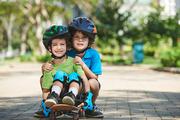 Cheerful brothers on helmets sitting on skateboard
