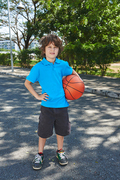 Curly little basketball player in blue polo T-shirt holding ball and looking at camera with deep black eyes in sunny park