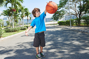 Funny little basketball player with dark curly hair bouncing ball in sunny park with palm trees, full-length portrait