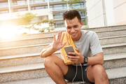 Happy jogger using smartphone to make videocall after training