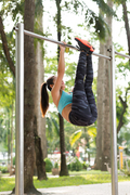 Young Asian woman exercising on chin-up bar