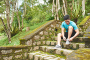 Asian sportsman sitting on steps in park and tying shoes
