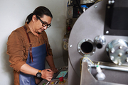 Asian man in glasses managing work of coffee roaster
