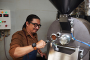Barrista using modern roaster to prepare coffee beans