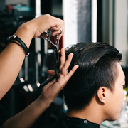 Close-up image of barber cutting hair with professional scissors