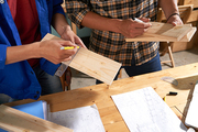Carpenters measuring wooden planks for the project