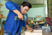 Vietnamese young carpenter driving screws with drill