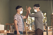 Vietnamese father and son giving high five after finishing work