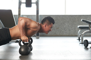 Sportsman using kettle bells when doing push-ups