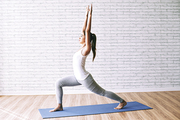 Slim fit woman practicing warrior yoga position