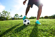 Unrecognizable sportsman with dark skin wrapped up in playing soccer, spacious football pitch illuminated with sunbeams on background