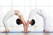 Side view of man and woman performing bridge exercise
