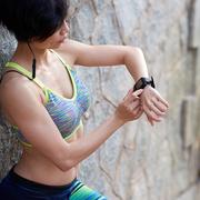 Sporty fir woman checking smart watch after outdoor training