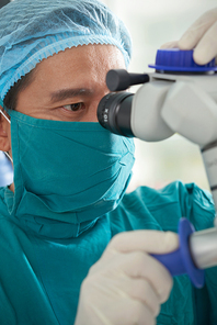 Female patient lying in operating room while team of surgeons in protective gloves putting a bandage on the eye after operation