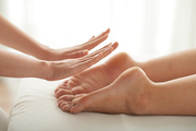 Feet of woman attending reiki therapy, selective focus