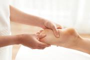 Unrecognizable female rubbing feet of female client while doing massage in spa salon