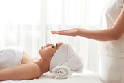 Reiki therapist holding hands over head of pretty female patient