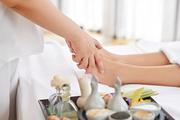 Woman receiving professional feet massage in spa salon