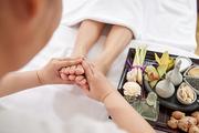 Woman receiving deep foot massage in spa salon