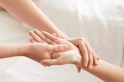From above shot of hands of anonymous therapist rubbing wrist and palm of female client during massage session in spa salon