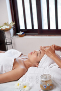 Beautiful woman relaxing at spa salon, she care for her face and getting a facial massage