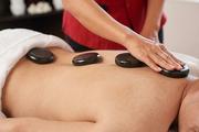 Hands of masseur applying hot basalt stones along spine of man