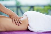 Hands od masseur massaging low back of female client