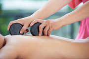 Hands of professional masseur doing massage with hot stones