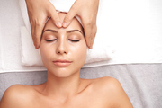 Relaxed young woman lying on white towel during procedure of spa massage with calming effect