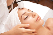 Relaxed woman enjoying facial beauty procedure carried out with special electric device