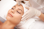 Young relaxed female having anti-wrinkle beauty procedure on face