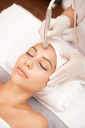 Relaxed woman lying in beauty salon and having anti-wrinkle therapy on her forehead
