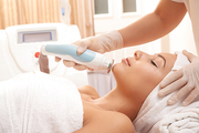 Cosmetologist using electronic tool for professional facial