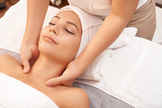 Young female lying on soft towels in spa salon and enjoying relaxing massage of her neck