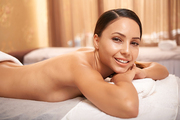 Happy young relaxed woman looking at camera while lying in spa salon after rejuvenation procedure