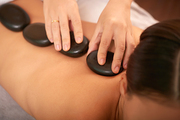 Back of young relaxed female having spa stone massage in modern bodycare salon