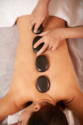 Overview of relaxed client back and hands of cosmetician putting spa stones before procedure