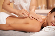 Masseuse hands touching back of relaxed client during massage in spa salon