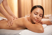 Smiling attractive woman lying on massage table with her eyes closed and enjoying procedure
