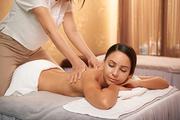 Beautiful young woman enjoying professional back massage in spa salon
