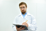 Portrait of young bearded doctor wearing glasses standing against white wall writing on clipboard, copy space