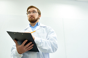 Low angle  portrait of young bearded doctor wearing glasses standing against white wall writing on clipboard, copy space