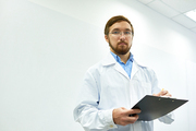 Low angle  portrait of  bearded doctor wearing glasses standing against white wall writing on clipboard and looking at camera, copy space