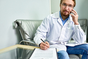 Portrait of friendly bearded doctor speaking by phone and looking at camera while signing contract form