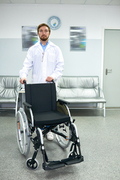 Portrait of young bearded doctor standing in hospital hall posing with empty wheelchair and looking at camera