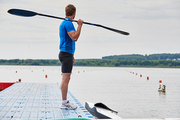 Young athlete in sportswear standing with paddle on the pier and looking at view of calm lake