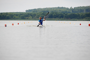 Young sportsman competing on rowing competition, he paddling on his kayak on the lake