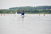 Young man splashing water while kayaking on river during rowing competition