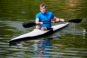 Young athlete floating on kayak on the river alone