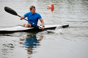 The athlete holding an oar and floating in kayak on the lake